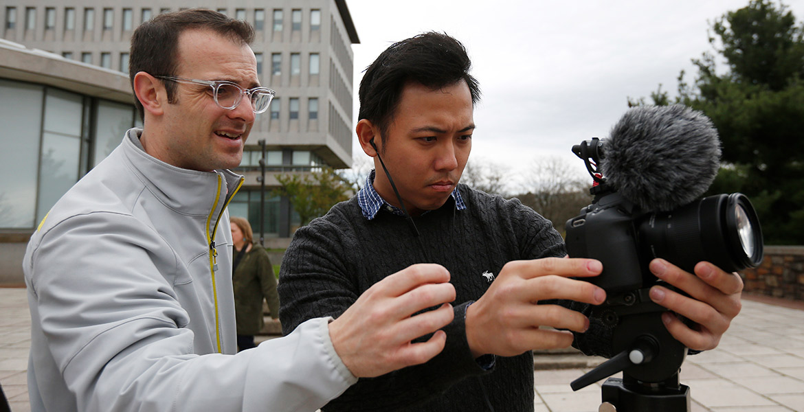 Matt Veto, professor of practice in journalism and communication and faculty adviser to The Brown and White, helping a student with a video camera
