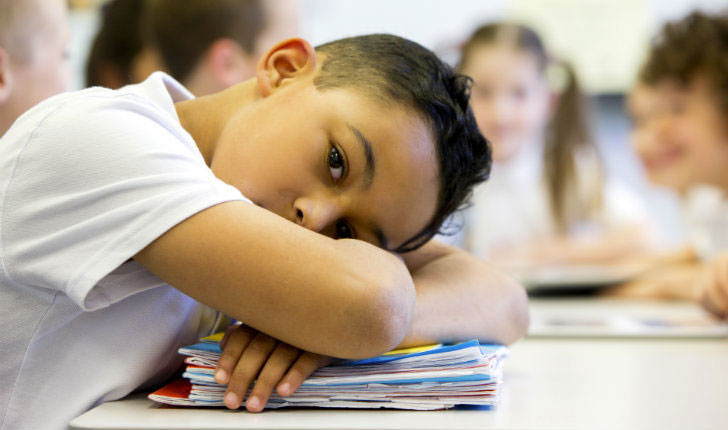 Student with head resting on desk