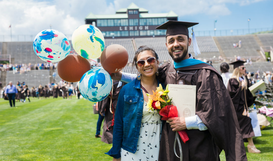 Graduate Kalim Abed stands with woman and holds balloons at Lehigh University commencement