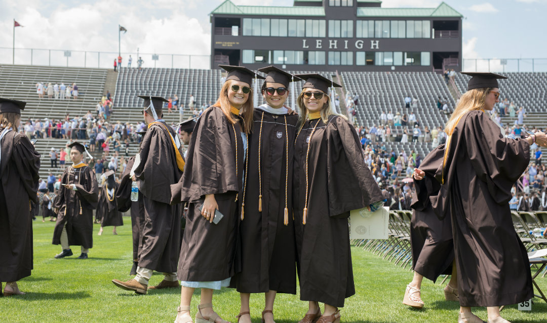 Three female graduates at Lehigh University commencement