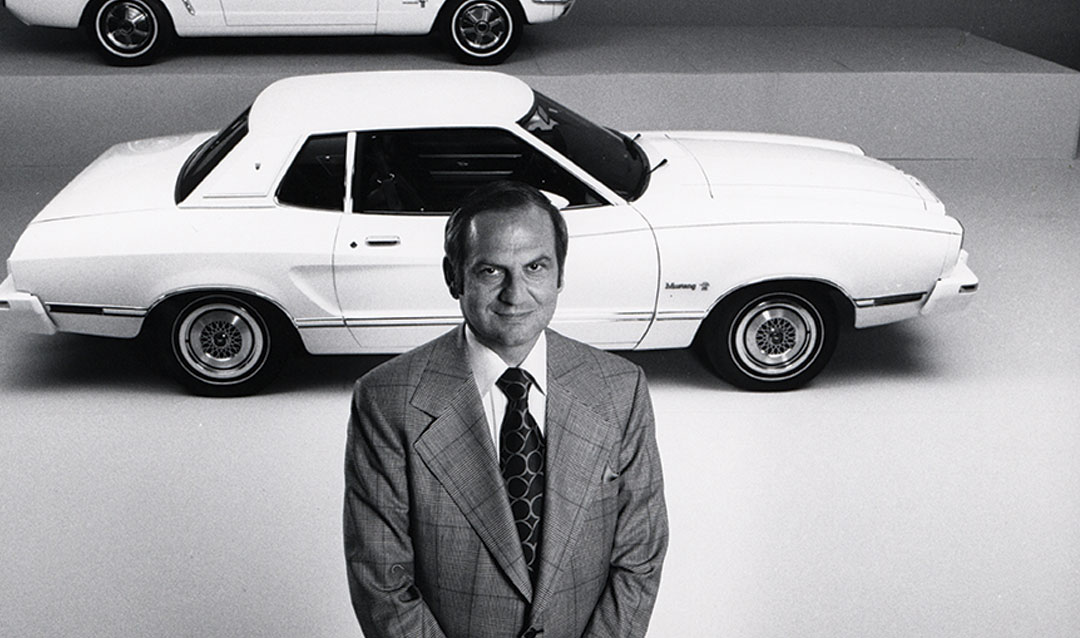 Lee Iacocca stands in front of Mustang