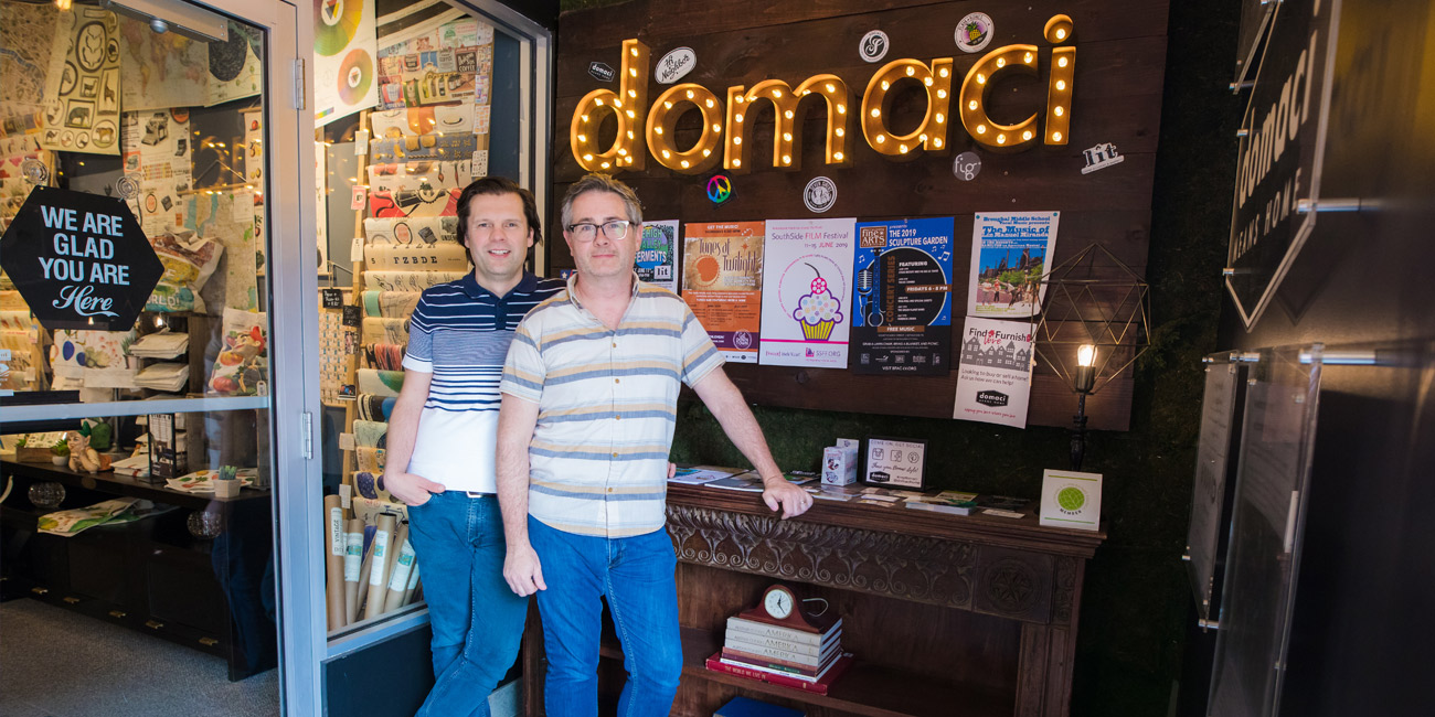 Two people standing in front of Domaci sign