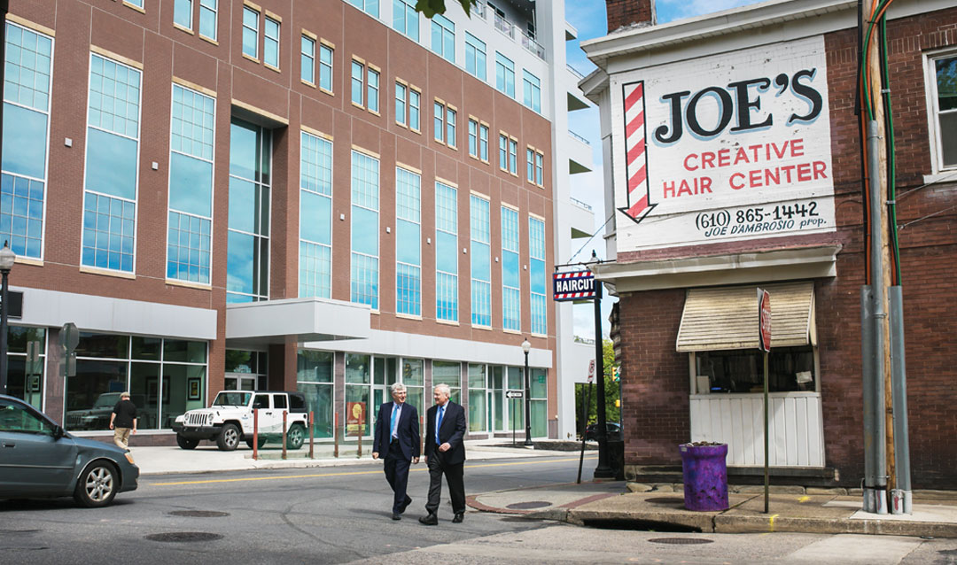 Lehigh President John D. Simon '19P and Bethlehem Mayor Robert Donchez walk between the Gateway at Greenway Park building (left) and Joe's Creative Hair Center, a South Side fixture.