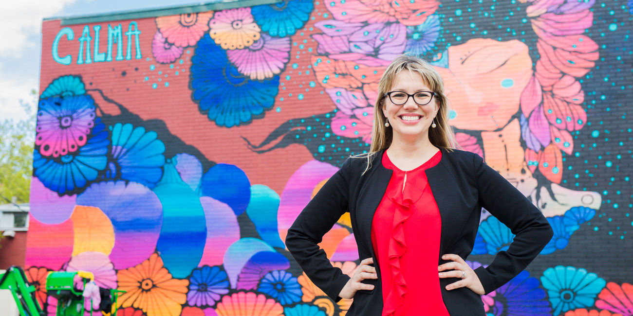 Missy Hartney standing in front of a mural