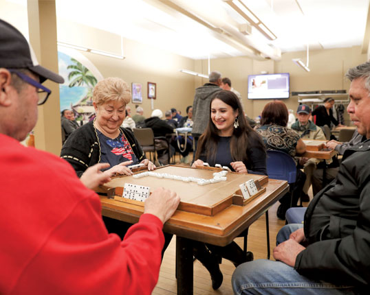 Students playing dominoes with seniors