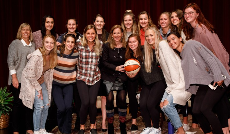 Cathy Engelbert poses with basketball and Lehigh University Women's Basketball team on stage at Gruhn Lecture.