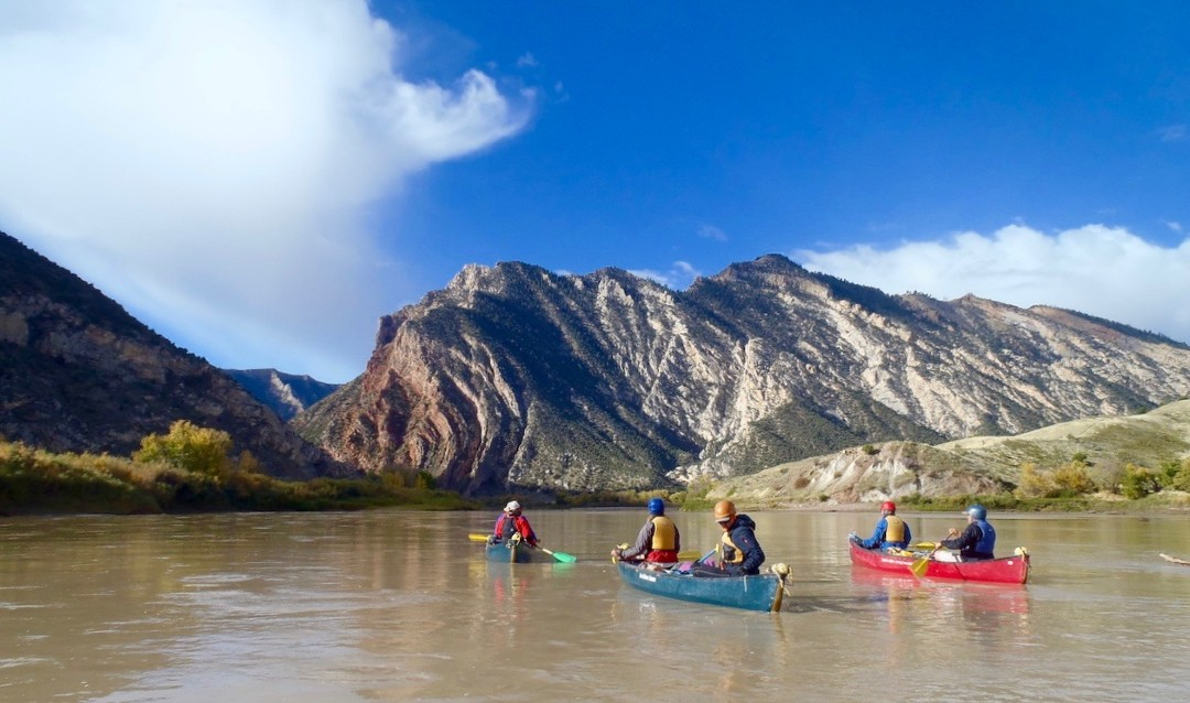 Group of people canoeing in Utah with view of mountains in the distance.