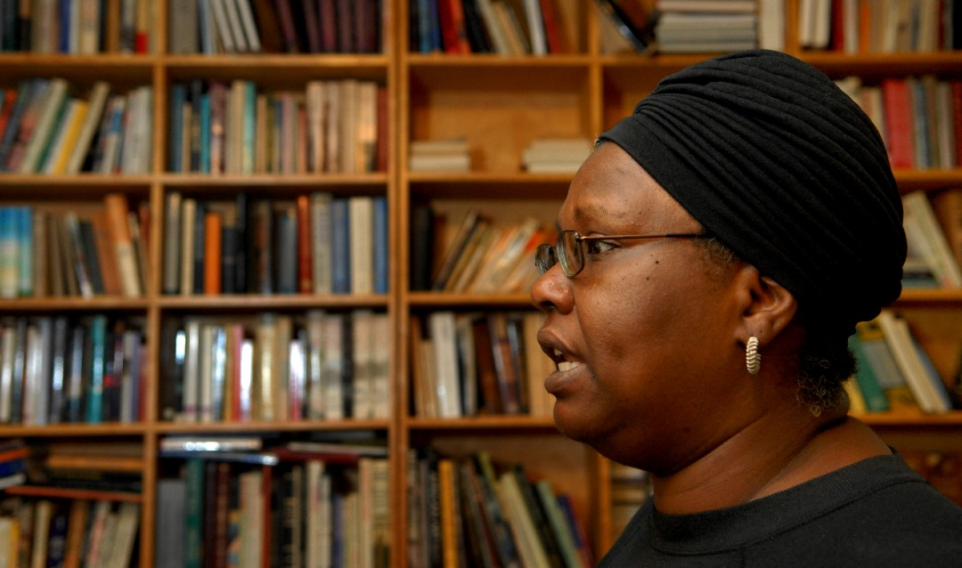 Image of writer Gloria Naylor in profile in front of bookshelf filled with books.