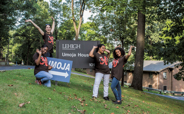 Students posing with the sign for the Umoja House