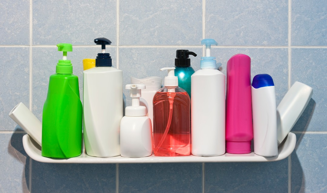 A collection of colorful shampoo bottles on a shower shelf