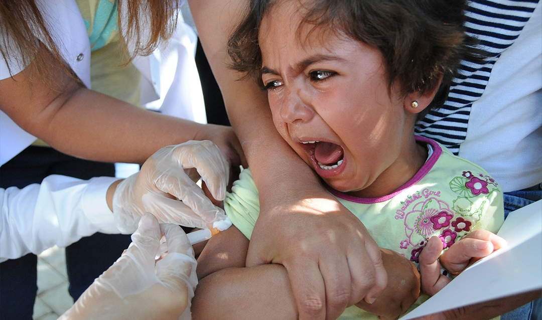 Young girl crying while receiving a vaccine