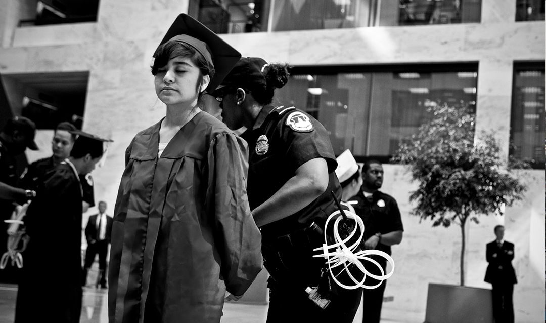 Photo of immigrant student in graduation cap and gown being handcuffed by police