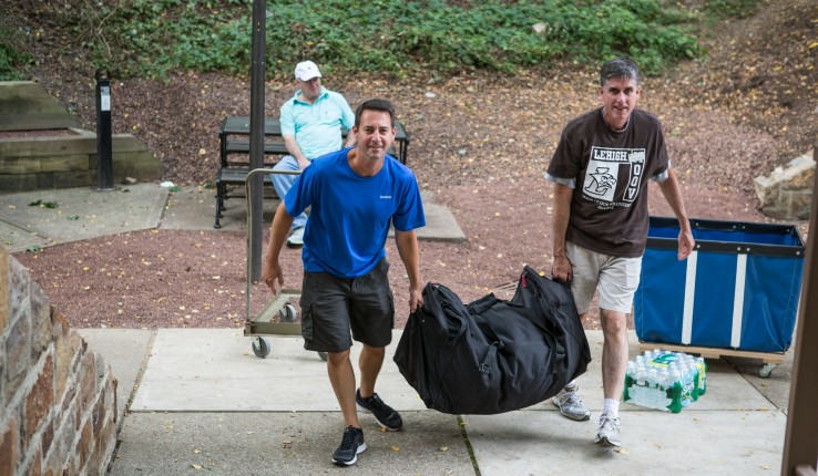 Lehigh Provost Patrick Farrell carries student belongings during move-in day