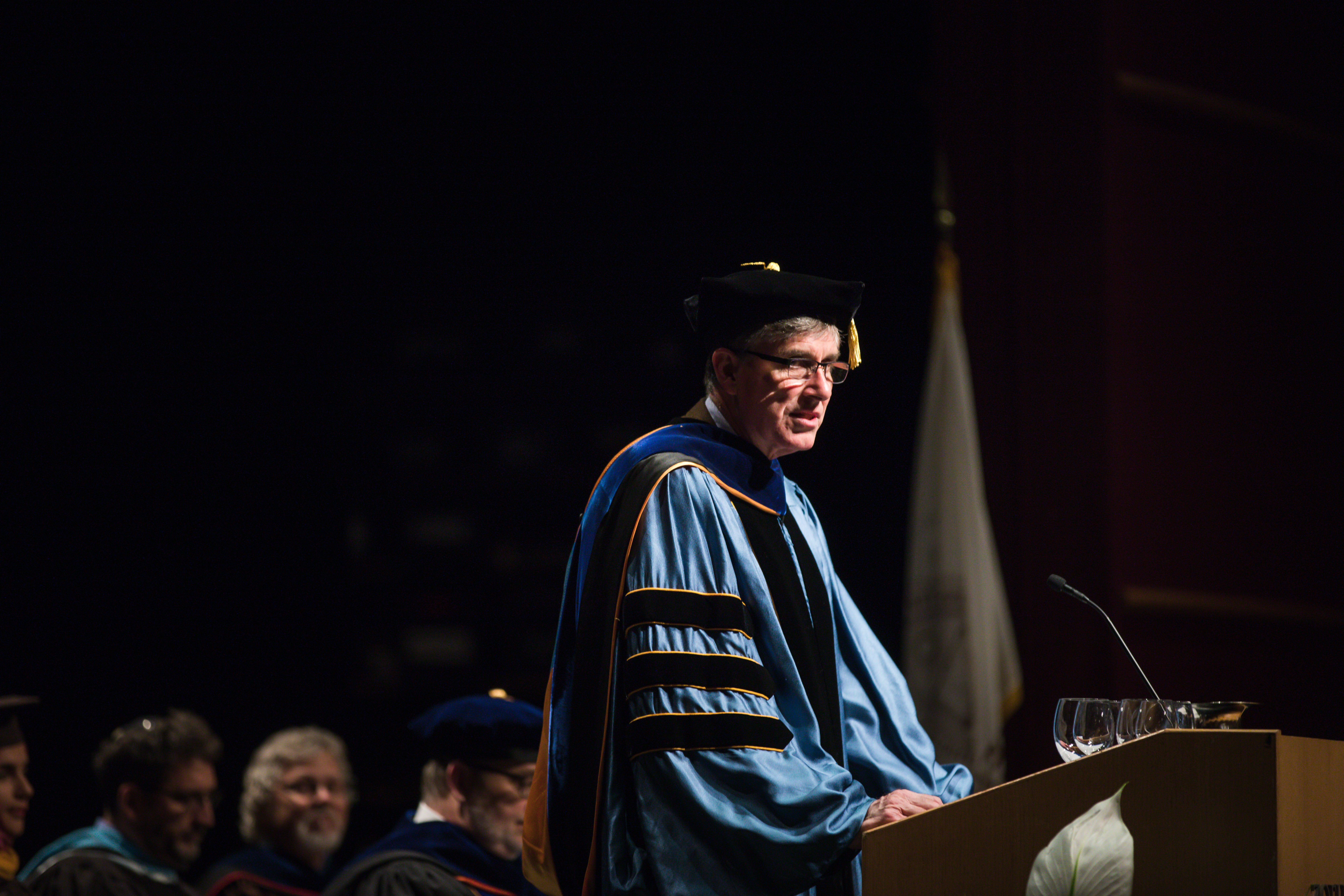 Lehigh Provost Pat Farrell speaks at the Honors Convocation while wearing regalia.